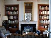 woonkamer met vaste boekenkasten en houtkachel