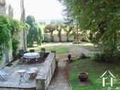 zicht vanuit het terras op ommuurde tuin