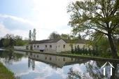 Grande maison le long du canal et grange